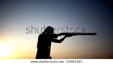 Woman shoots with his gun silhouette - stock photo