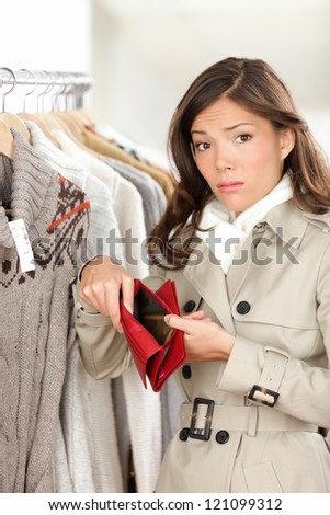 Woman shopper holding empty wallet or purse while shopping in store. Sad young woman looking at camera in clothing shop.