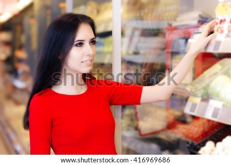 Woman Shopping at Shelf in Supermarket Store - Portrait of a young girl in a market store looking for best product and offer  - stock photo