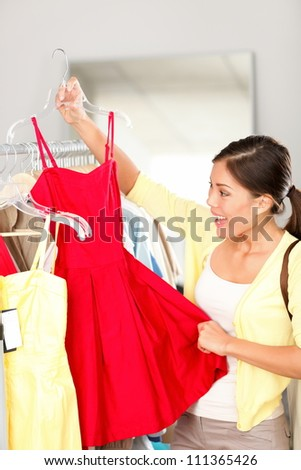 Woman shopping buying clothing holding red dress smiling happy and excited during sale in clothing store. Beautiful young multi-ethnic Caucasian / Asian Chinese woman shopper. - stock photo