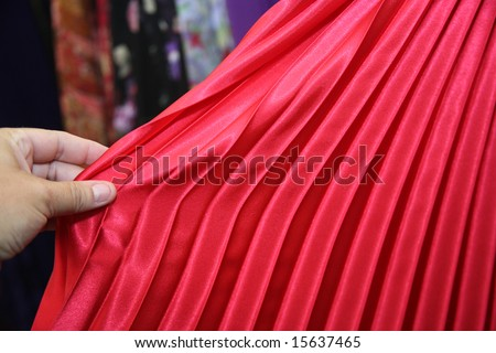 Woman shopping for clothing and inspecting a red pleated skirt or dress