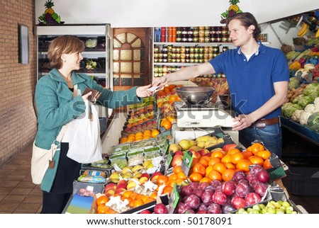 Woman shopping for fresh food and vegetables at a greengrocers' market - stock photo