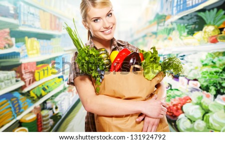 woman shopping for fruits and vegetables in produce department of a grocery store/supermarket - stock photo