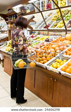 Woman shopping for fruits at grocery store - stock photo