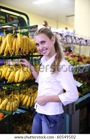 Woman shopping for fruits in the supermarket buying bananas - stock photo