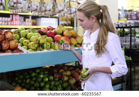 Woman shopping for fruits in the supermarket holding a lime - stock photo