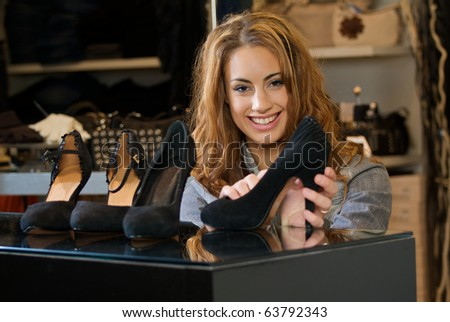 Woman shopping in a cloth shop lokking at some shoes