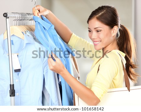 Woman shopping in clothing store looking at clothes smiling happy. Mixed race Asian Chinese / Caucasian young casual woman shopper. - stock photo