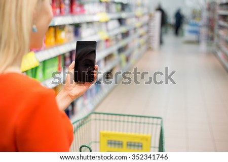 Woman shopping in supermarket and using mobile device  - stock photo