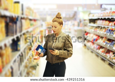 Woman shopping in supermarket reading product information. Checking list. - stock photo