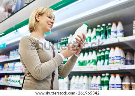 Woman shopping milk in grocery store