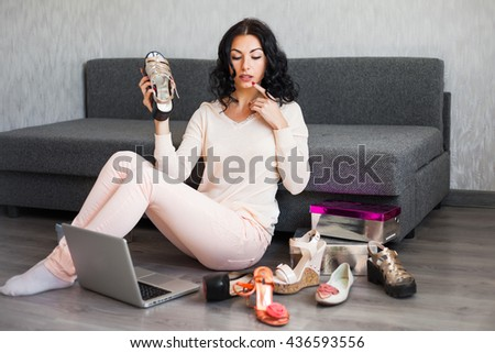 Woman shopping on computer and credit card sitting on the floor smiling happy. Pretty cheerful caucasian woman shopper buying spending money on-line on internet relaxing in couch at home. - stock photo