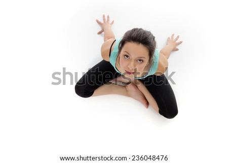 Woman shot from a birds eye view looking down doing yoga and stretching  exercises - stock photo