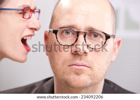 woman shouting in man's ear maybe in a business environment like an office or a meeting room - stock photo