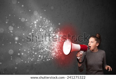 Woman shouting into megaphone and glowing energy particles explode concept - stock photo