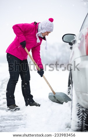 Woman  shoveling and removing snow from his car during a snowing - stock photo