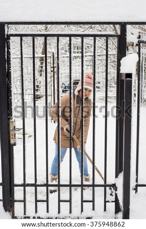 Woman shoveling snow by fence and smiling - stock photo
