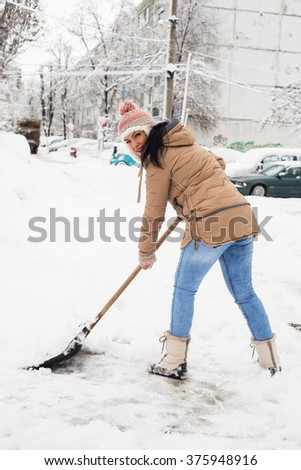 Woman shoveling snow in parking in cold day in winter - stock photo