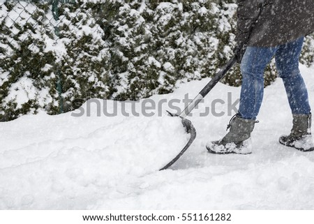 Woman shoveling snow on pavement