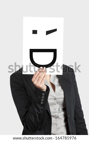 Woman showing a blank paper with a smile winking in front of her face - stock photo