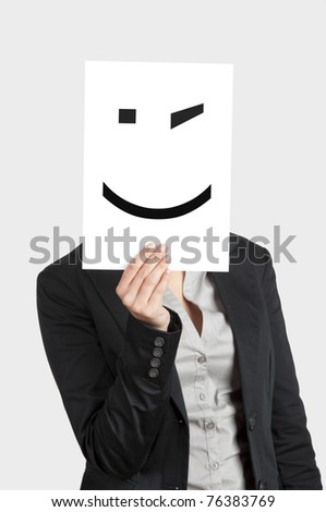 Woman showing a blank paper with a smile winking in front of her face