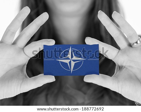 Woman showing a business card, NATO symbol - stock photo