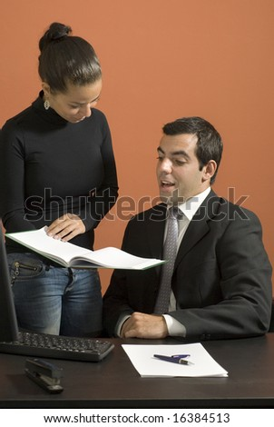 Woman showing a businessman paperwork as he looks surprised. Vertically framed photo. - stock photo
