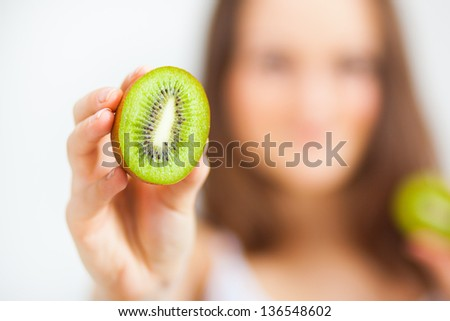 Woman showing a kiwi. Soft focus
