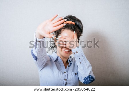 Woman showing a stop, eyes with her hand closed. On a gray background. - stock photo