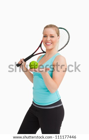 Woman showing a tennis ball in her hand against white background