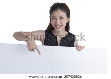 Woman showing and pointing at blank billboard sign banner, Young smiling Chinese Asian / Caucasian female model. Isolated on white background. - stock photo