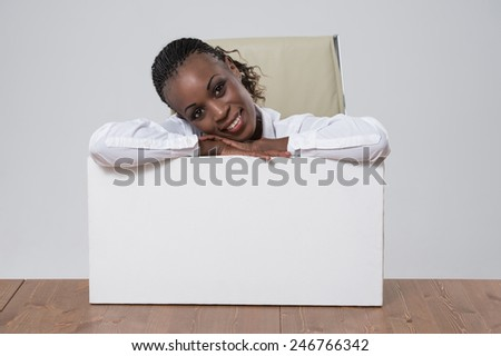 Woman showing blank card sitting at workplace at office