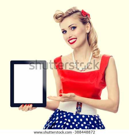 woman, showing blank no-name tablet pc monitor, with copyspace, dressed in pin-up style dress in polka dot. Caucasian blond model posing in retro fashion vintage shoot.