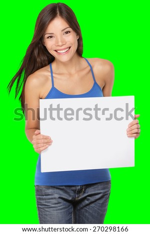 Woman showing blank paper sign whiteboard. Fresh, happy and joyful multiracial girl in her twenties showing copy space for your message. Isolated on green screen chroma key background in studio. - stock photo
