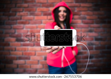Woman showing blank smartphone screen over brick wall. Focus on smartphone