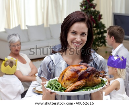 Woman showing Christmas turkey for family dinner at home - stock photo