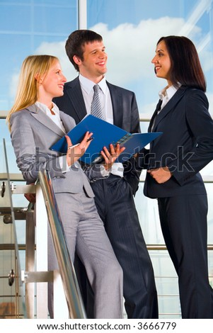 Woman showing documents to her colleagues on stairs in the building with glassy walls - stock photo