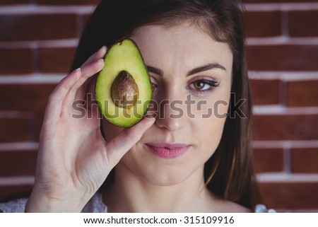Woman showing fresh avocado on red brick background