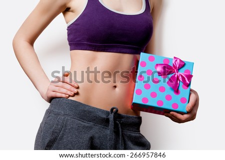 Woman showing her abs with gift box after weight loss on white background - stock photo
