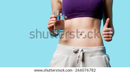 Woman showing her abs with water glass after weight loss on blue background - stock photo