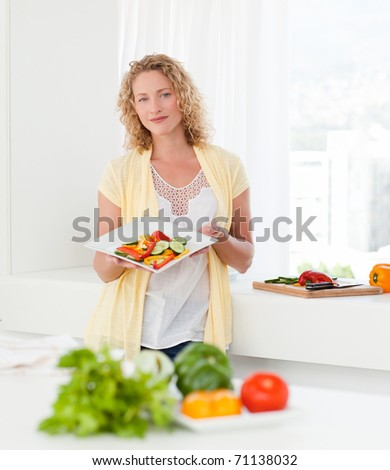 Woman showing her healthy food  in her kitchen at home - stock photo