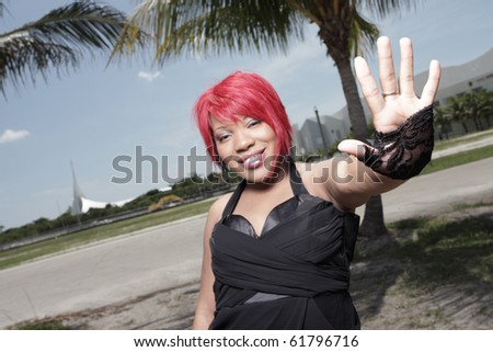Woman showing her palm and smiling - stock photo