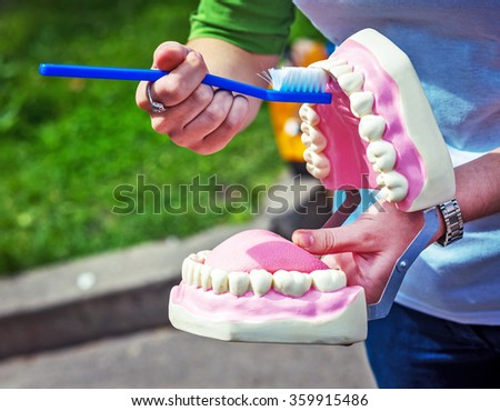 Woman  showing on a jaw model how to clean the teeth with tooth brush properly and right - stock photo