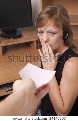Woman showing surprise at getting a pink slip. Termination or layoff notice. - stock photo