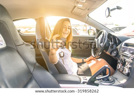 woman showing the keys inside a sport car. sexy business woman ready to drive. concept about transportation - stock photo
