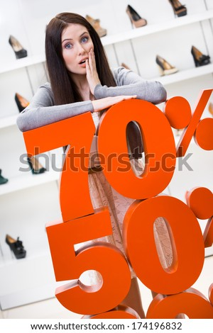 Woman showing the percentage of sales on footwear in the shopping center against the window case with pumps - stock photo