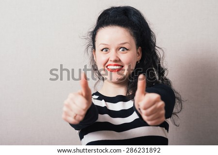 Woman showing thumbs up gesture well, okay. Gray background - stock photo