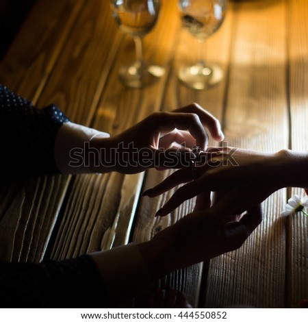 Woman shows engagement ring on hand to friend on wooden table background