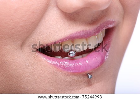 woman shows her  piercing - stock photo