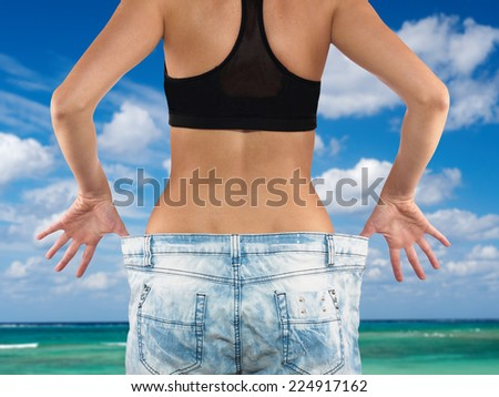 woman shows her weight loss by wearing an old jeans - stock photo